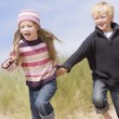 Two young children running on beach holding hands smiling — Stock Photo #4771511