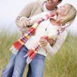 Couple standing on beach smiling - Stock Photo