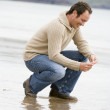 Man crouching on beach smiling — Stock Photo