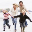 Stock Photo: Family running on beach holding hands smiling