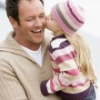 Father holding daughter kissing him at beach smiling - Stockfoto