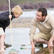 Father and son at beach fishing — Stock Photo