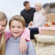 Family at beach with picnic smiling — Stock Photo #4771579