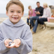 Family at beach with picnic smiling focus on boy with seashells — Stock Photo #4771581