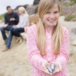 Family at beach with picnic smiling focus on girl with seashells - Stock Photo