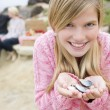 Family at beach with picnic smiling focus on girl with seashells - Stock fotografie