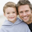 Father and son at beach smiling — Stock Photo