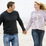 笑みを浮かべて手を繋いでいるビーチで歩くカップル — ストック写真