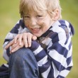 Young boy sitting outdoors dirty and smiling - Stock Photo