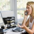 Woman in home office with computer using telephone frowning - Photo
