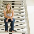 Woman sitting on stairs smiling — Stock Photo