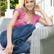 Woman sitting outdoors on patio smiling — Stock Photo