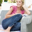 Woman sitting outdoors on patio smiling — Stock Photo #4771684