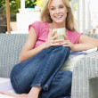 Woman sitting outdoors on patio with coffee smiling - Stock Photo