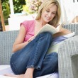 Woman sitting outdoors on patio with book smiling — Stock Photo