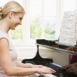 Woman playing piano and smiling — Stock Photo #4771729