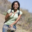 Woman crouching on beach path smiling — Stock Photo
