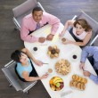 Four businesspeople at boardroom table with breakfast smiling — Stock Photo