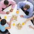Four businesspeople at boardroom table with sandwiches - Foto Stock