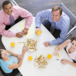 Four businesspeople at boardroom table with sandwiches smiling — Stock Photo #4771912