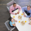 Four businesspeople at boardroom table with sandwiches smiling — Stock Photo