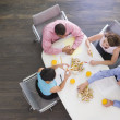 Four businesspeople at boardroom table with sandwiches — Stock Photo #4771915