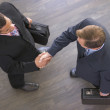 Two businessmen indoors shaking hands — Stock Photo
