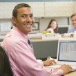 Businessman in cubicle using laptop and smiling — Stock Photo