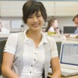 Businesswoman in cubicle smiling — Stockfoto
