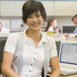 Businesswoman in cubicle smiling — Stock Photo #4771975
