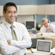 Businessman standing in cubicle smiling — Stock Photo