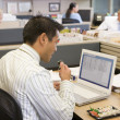 Stock Photo: Businessmin cubicle at laptop eating sushi
