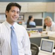 Stock Photo: Businessmstanding in cubicle smiling