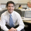 Businessman in cubicle smiling — Stock Photo