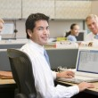 Businessman in cubicle with laptop smiling — Stock Photo #4771994