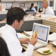 Businessman in cubicle at laptop eating sandwich — Stock Photo