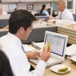 empresário em cubículo em laptop comendo sanduíche — Foto Stock