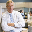 Businessman standing in cubicle — Stock Photo