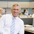 Businessman in cubicle smiling — Stock Photo #4772000