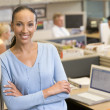 Businesswoman standing in cubicle smiling — Stock Photo #4772001