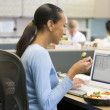 Businesswoman in cubicle eating sushi smiling — ストック写真