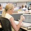Businesswoman in cubicle using laptop eating sushi - Stockfoto
