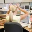 Businesswoman in cubicle with laptop and stacks of files - Stockfoto