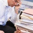 Businessman in cubicle with laptop and stacks of files — Stock Photo