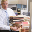 Stock Photo: Businessmstanding in cubicle holding stacks of files