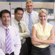 Foto Stock: Business team standing in cubicle smiling