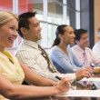 Five businesspeople at boardroom table smiling - Stock Photo