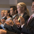 Five businesspeople applauding and smiling in presentation room - Stock Photo