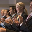 Five businesspeople applauding and smiling in presentation room — Stock Photo #4772062