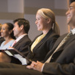 Five businesspeople smiling in presentation room with clipboards — Stock Photo #4772064